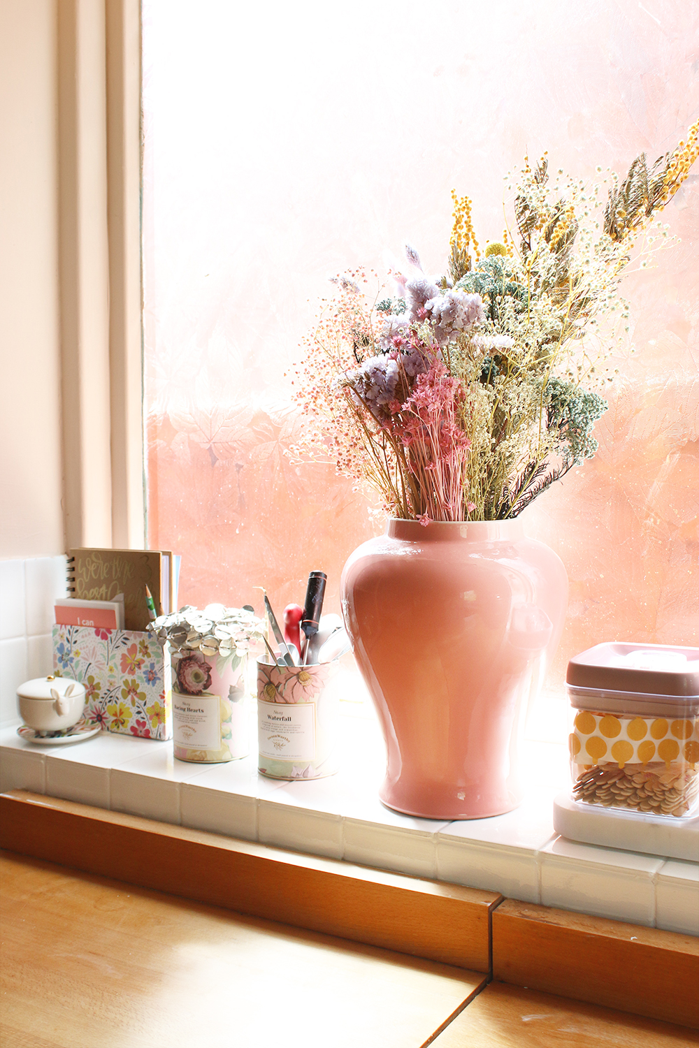 window sill recess in peach with dried flowers and supplies