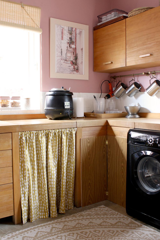 mustard yellow curtain under worktops in pink kitchen