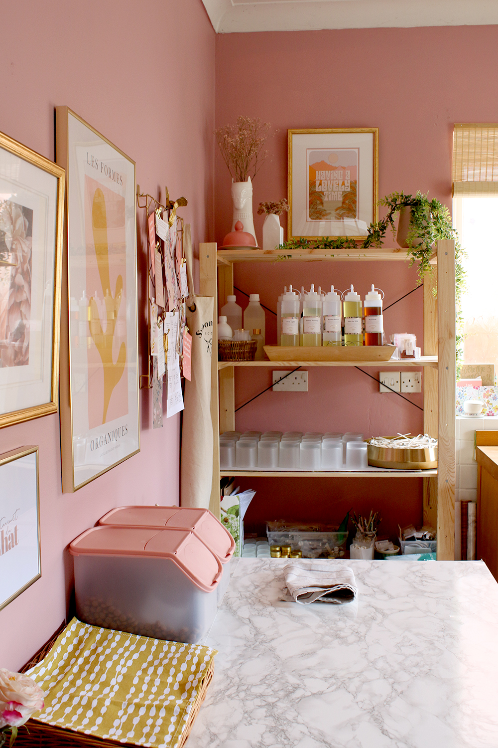pink and yellow pet station with gallery wall and utility room shelving