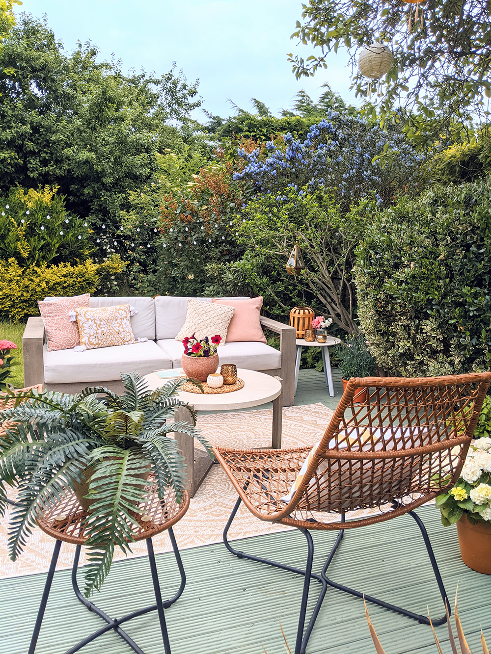 garden sofa and rattan chairs on green willow deck