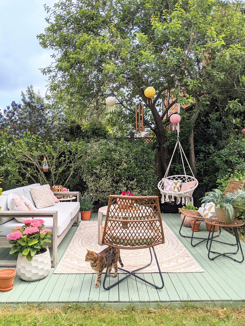 Decked area with hanging chair styled in pink and green garden