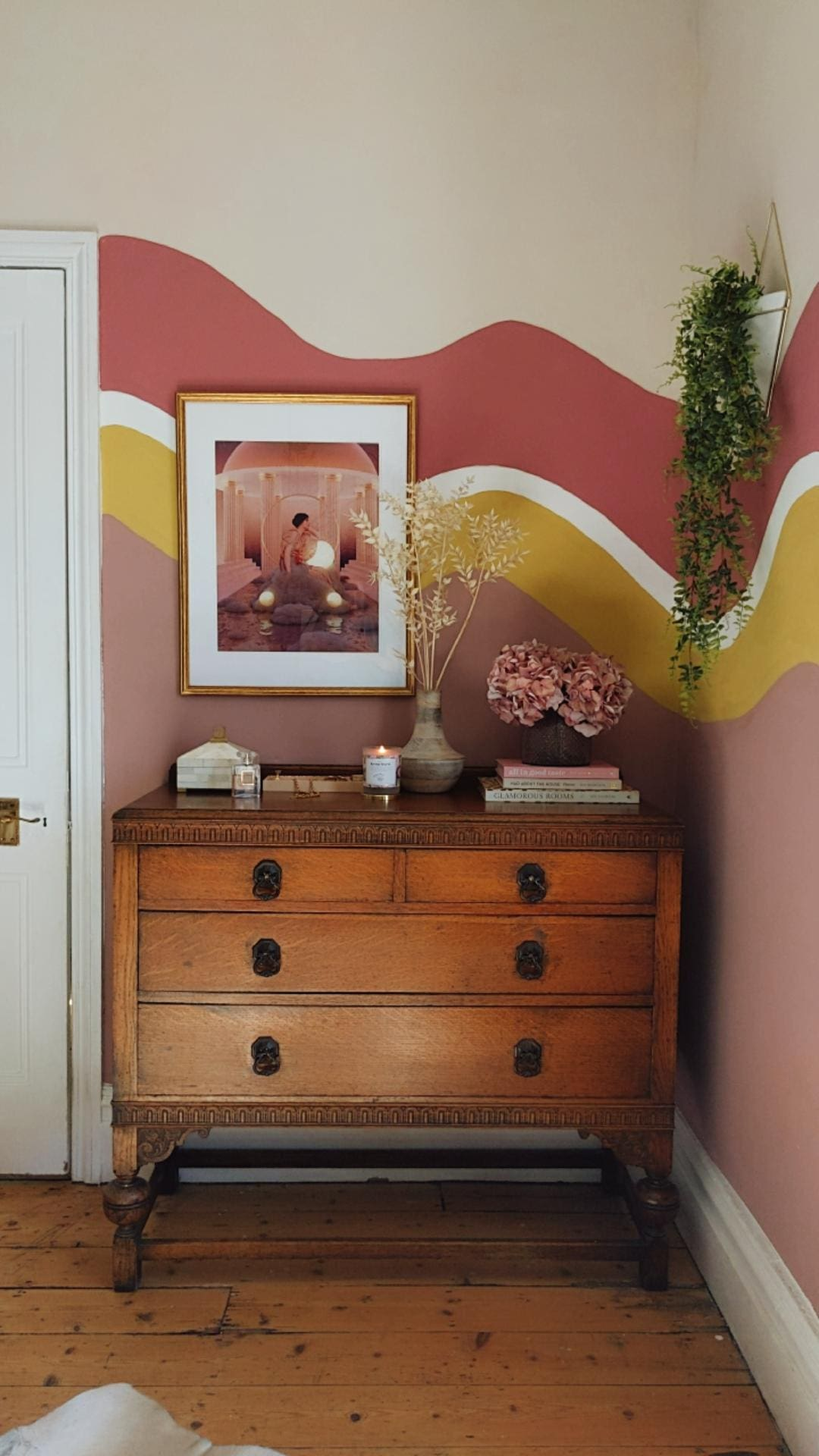 Wall painted in organic colour blocks of pink and yellow with vintage chest of drawers