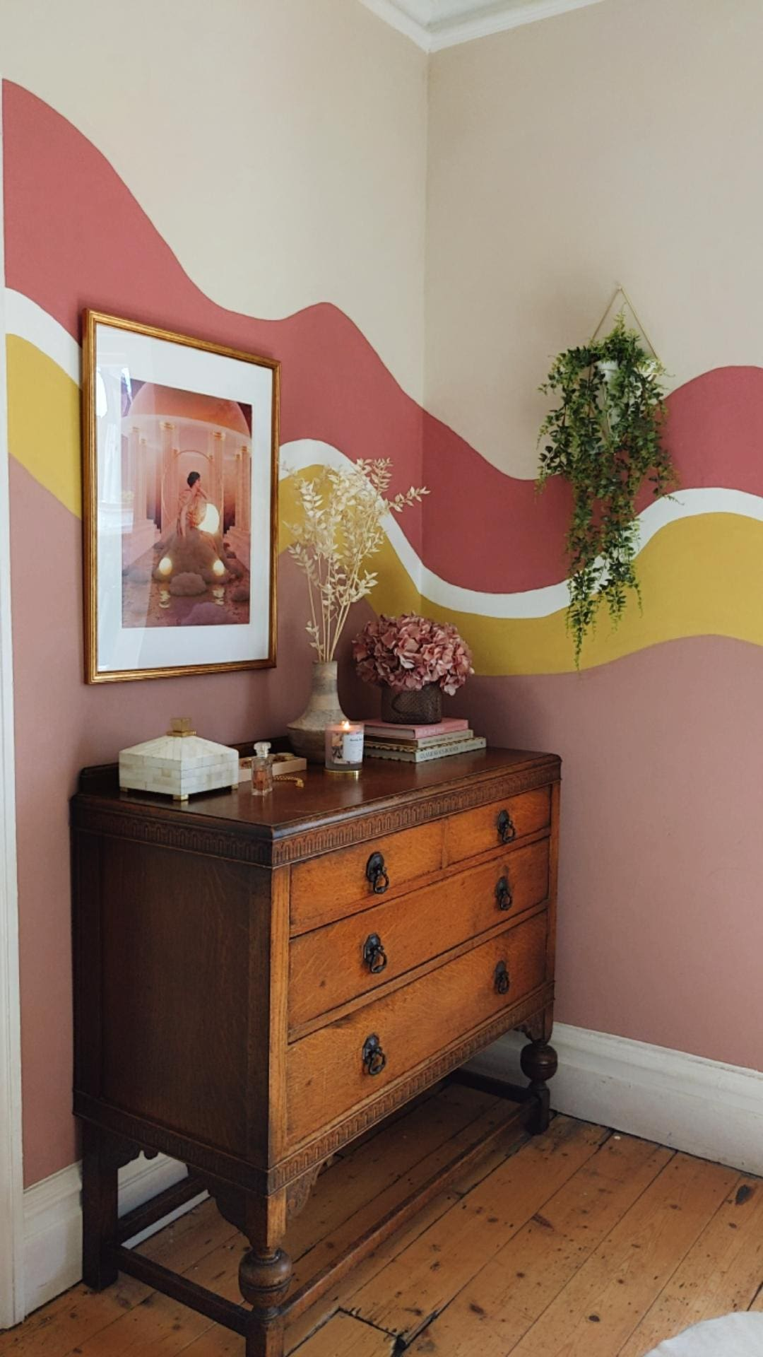 Organic free form colour blocks on wall in pinks and yellow with vintage chest of drawers and dried flowers