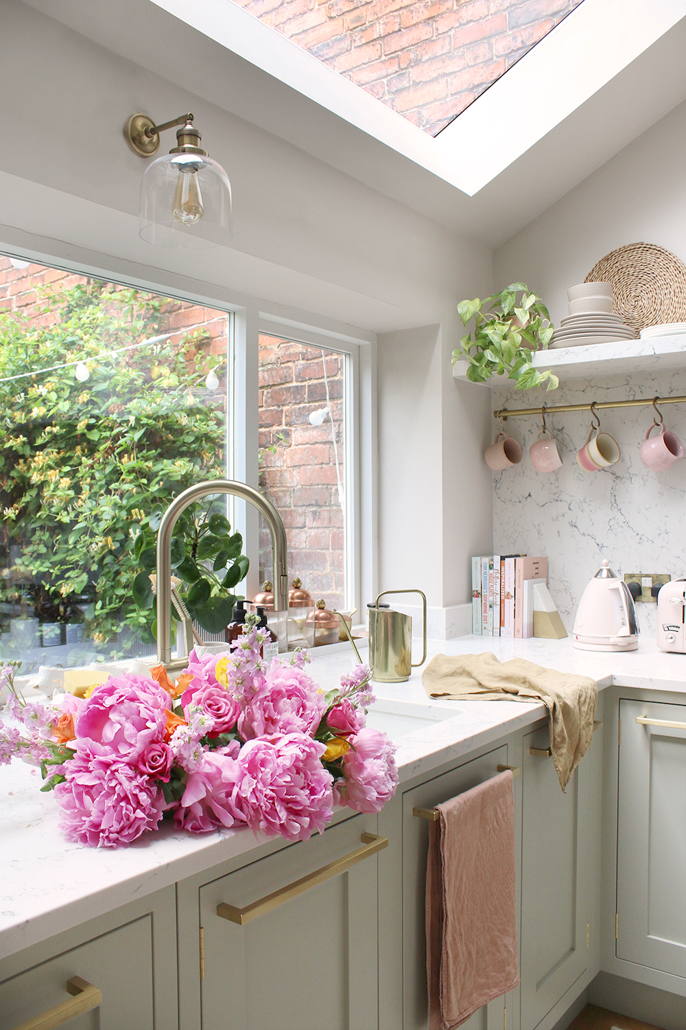 green and marble kitchen with pink peonies in the sink