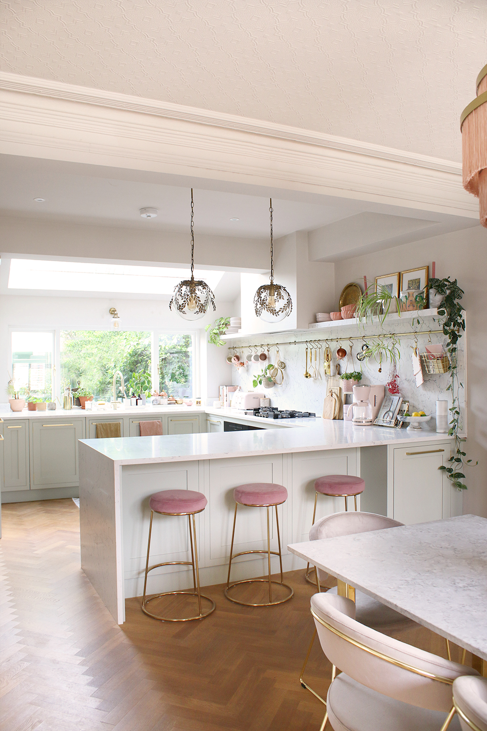 pink and pale green kitchen with marble worktops and vintage lighting