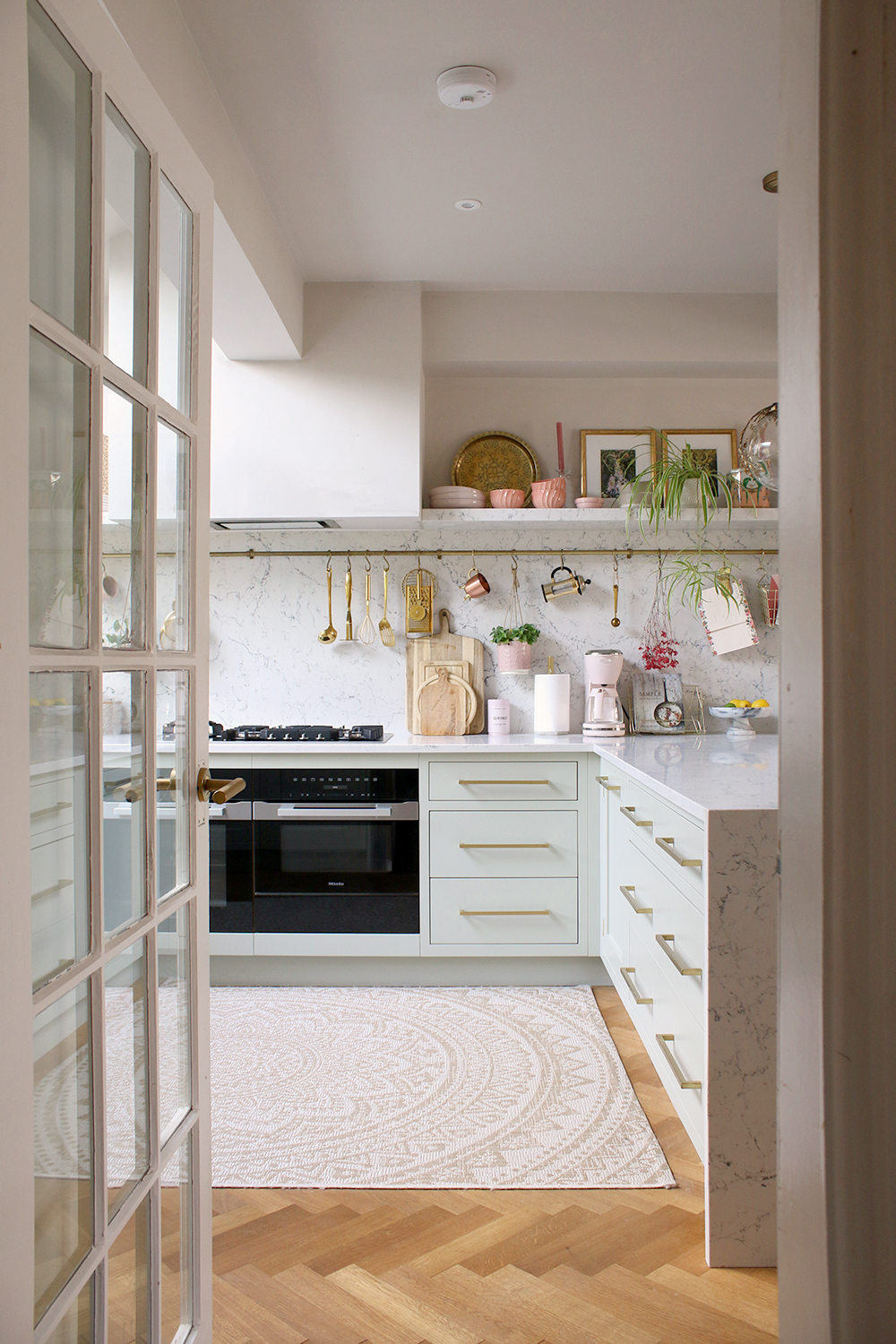 kitchen with sage green cabinets and marble worktops with floating shelf
